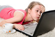 Young girl is lying on the floor and working on a laptop