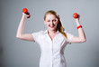 Merry successful businesswoman with raised dumbbells.
