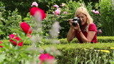 Blond woman taking pictures of flowers