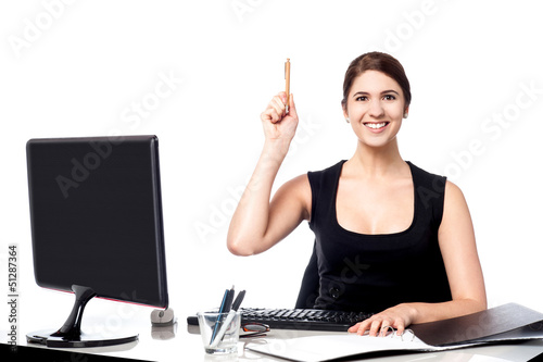 Businesswoman holding pen and raising her hand