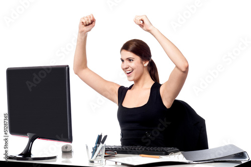Excited business woman raising her hands.