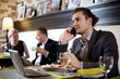 The businessman using the laptop and mobile in cafe.
