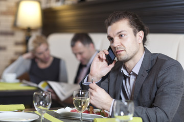 The attractive white person with use of its phone at restaurant