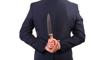 Businessman holding knife behind his back.