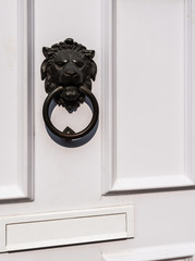 Closeup of a white front door with knocker