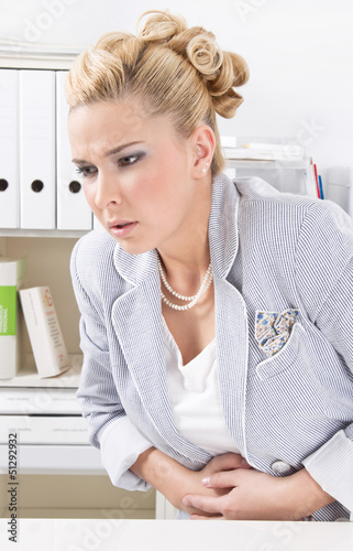 Frau im Büro hat Regelschmerzen