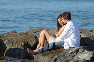 Couple flirting and hugging beside the sea