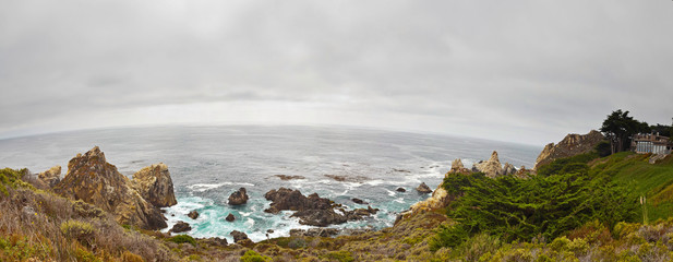 Panorama of Big Sur rocky coast with vegetation. Cloudy sky. USA