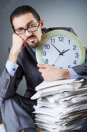Man with clock and pile of papers