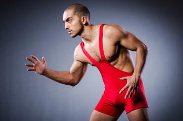 Young wrestler in dark studio