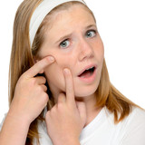 Teen girl looking skin spotted pimple squeezing poster