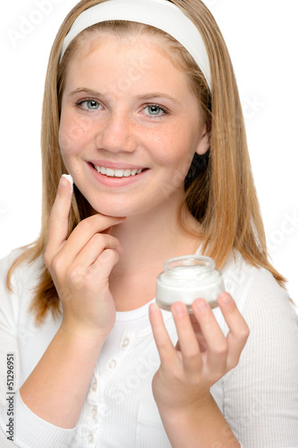 Cheerful young girl applying moistuizer face cream
