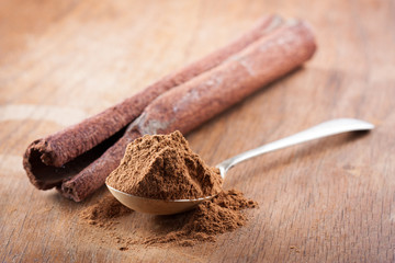 Cinnamon powder on a spoon with a stick of natural cinnamon