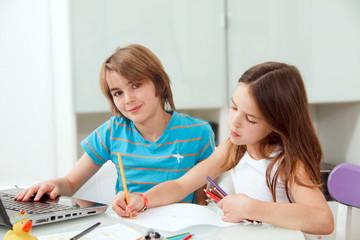 Kids daheim in ihrer Freizeit mit Notebook und Zeichenblock