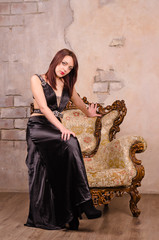 Young woman sitting on the arm of a fancy chair