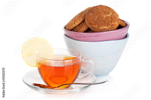 Glass cup of black tea with lemon and cookies
