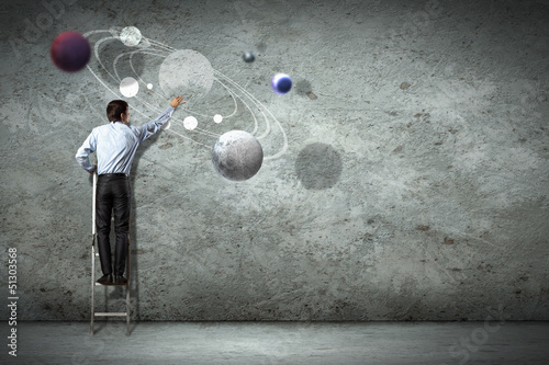 Business man drawing planets
