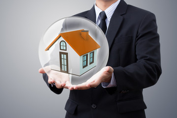 hands saving small house in crystal ball