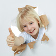 Cute girl with a smile shows thumb up through paper hole