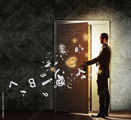 Young businessman opening door