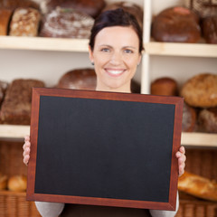 bäckereiverkäuferin zeigt leere tafel