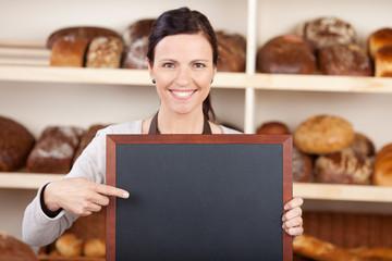bäckereiverkäuferin zeigt auf tafel
