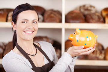 lächelnde verkäuferin mit sparschwein