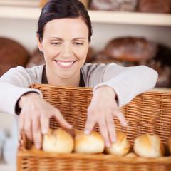 bäckereiverkäuferin sortiert brötchen