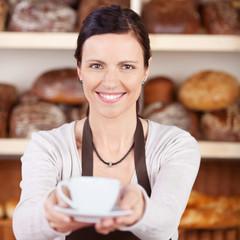 verkäuferin serviert kaffee in der bäckerei