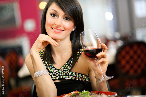 Woman tasting red wine in a restaurant