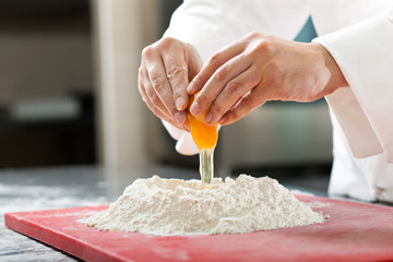 A baker cracking an egg into a pile of flour.