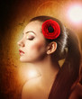 Profile of makeup woman with red flower in hair on  background