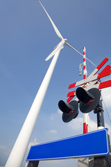 Railroad crossing with blue sky and windturbine