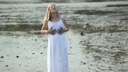 Young girl playing on a muddy beach while wearing a white dress