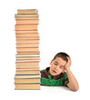 Little child sleeping behind stack of books isolated on white