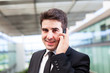 Closeup portrait of smiling young business man using cell phone