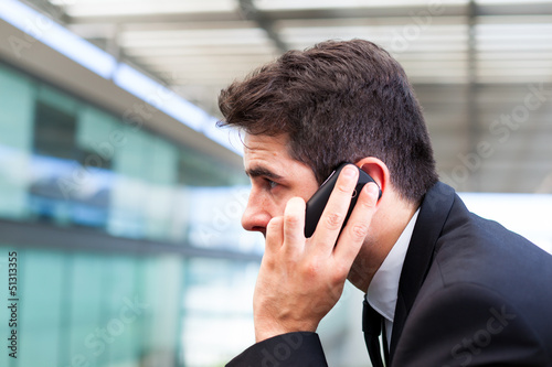 Closeup portrait of handsome business man using cell phone at th