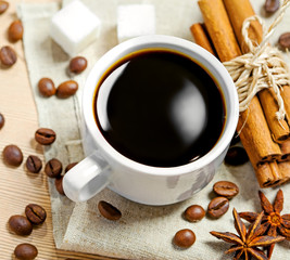 Coffee cup, beans, cinnamon, sugar and anise on a table