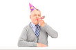 Mature man with party hat blowing