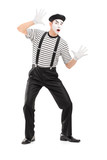 Full length portrait of a male mime artist performing