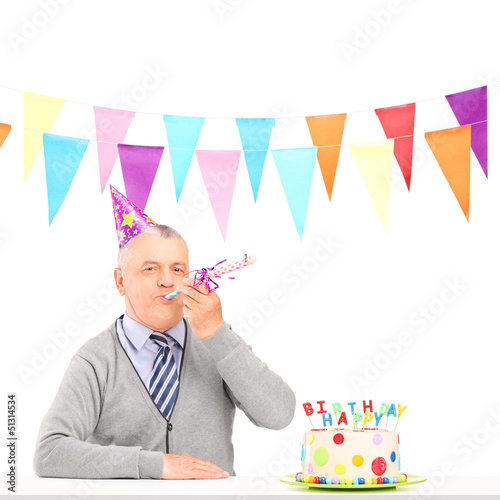 A happy mature man with party hat blowing and a birthday cake