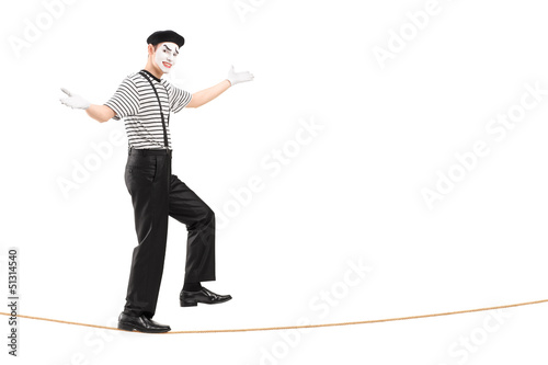 Full length portrait of a male mime artist walking on a rope