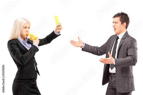 Woman in business suit showing a yellow card and blowing a whist