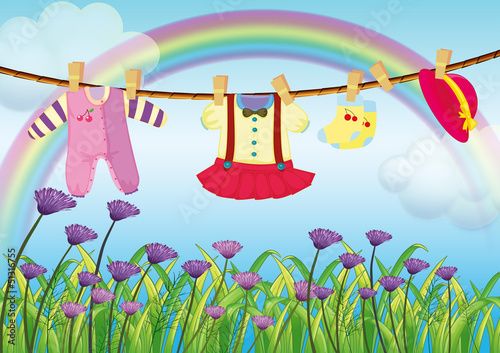 Hanging baby clothes near the garden with fresh flowers