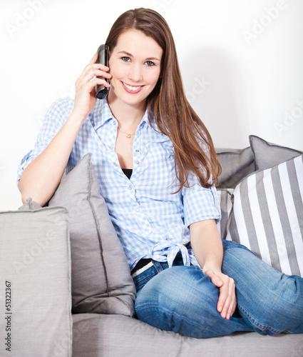 Attraktive Frau telefoniert zuhause auf der Couch