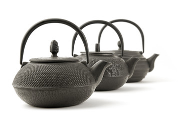 3 black iron teapots