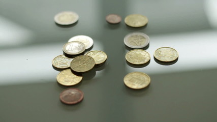 Slow motion shot of hand throwing euro coins on the table
