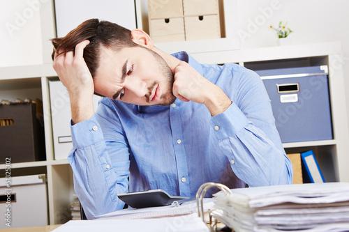 Nachdenklicher Mann im Büro mit Taschenrechner