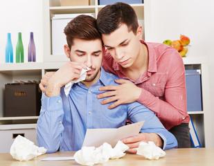 Schwuler weinender Mann liest Brief und wird getröstet