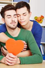 Schwules Paar mit Herz kuschelt
